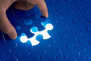 Hand holding the last piece of jigsaw puzzle